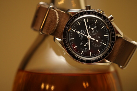 Omega Speedmaster watch on leather nato strap wrapped around bottle of single malt scotch on brown background