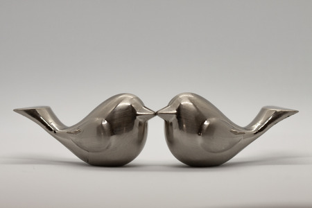 Two silver love bird figurines kissing on gray background Stockfoto