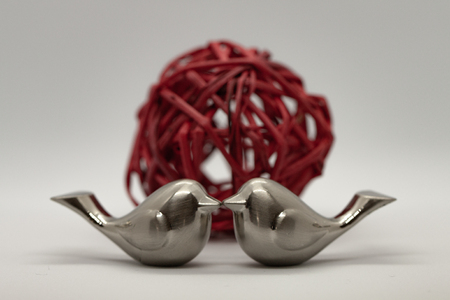Two silver love bird figurines kissing in front of red ball on gray background