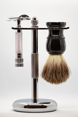 Stainless steel double edge safety razor and badger hair shaving brush hanging from polished stainless steel stand on gray background Фото со стока