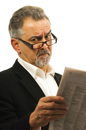 appalled: Mature man with glasses reads his newspaper with an appalled look on his face.