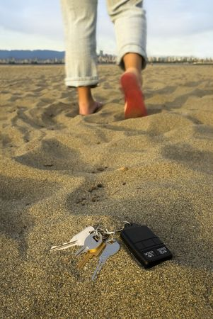 flops: A person walks away leaving their keys in the sand at the beach. Stock Photo
