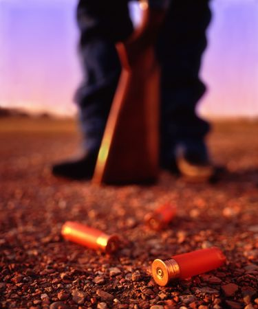 Three spent shotgun shells lay on the ground in front of a person standing with a shotgun. Very narrow depth of field, focused on the front shotgun shell.