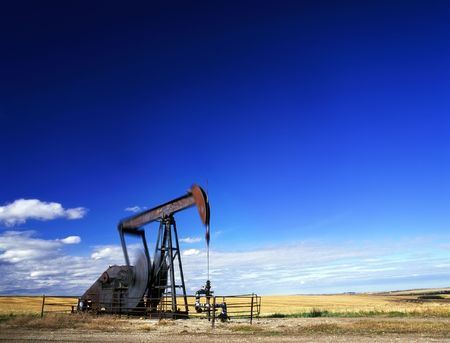 An oil well with the pump jack in action. Located in the province of Alberta, Canada.