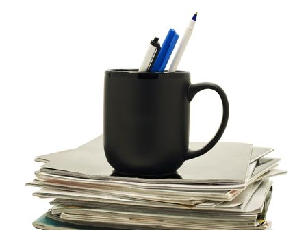 A black mug holds three pens on top of a stack of magazines.