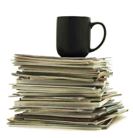 Black mug sitting on top of a stack of magazines Stock Photo - 6786281