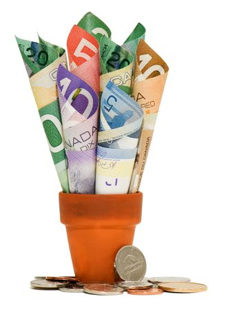 canadian cash: Canadian bills rolled up in a terra cotta pot with coins at the base.