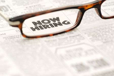 hiring: Now Hiring classified ad showing through reading glasses.