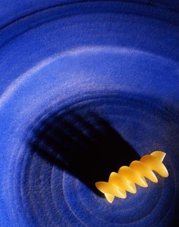 Single piece of rotini pasta sits on a blue plate casting an interesting  shawdow. Standard-Bild