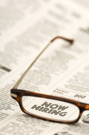 NOW HIRING: Classified ad showing through reading glasses. photo
