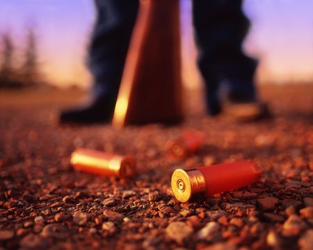 Shotgun shells at the feet of a hunter holding a shotgun.