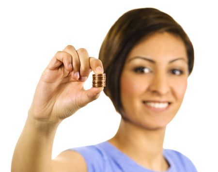 Young, pretty ethnic woman pinches a stack of pennies. Photographed with a white background of +2 EV. Standard-Bild