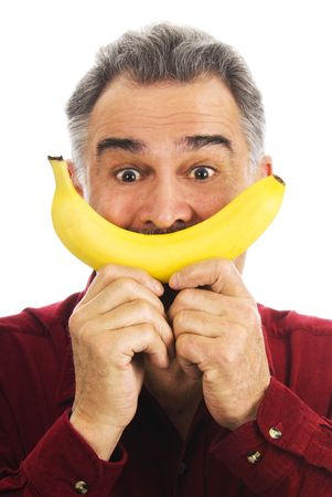 Mature man, wearing a red shirt, holds a yellow banana with two hands to his face, representing a smile. photo