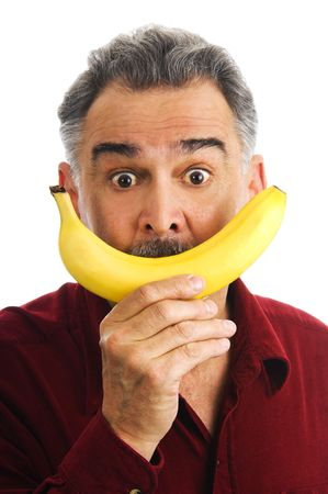 Mature man, wearing a red shirt, holds a yellow banana to his face, representing a smile. photo