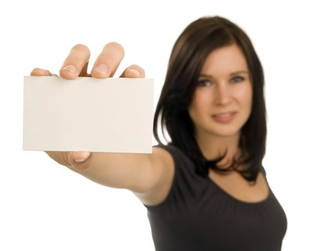 business card in hand: Brunette woman holds a blank, horizontal, business card at arms length. Focus is on the card, with face out of focus.