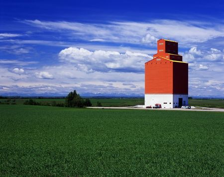 An orange grain elevator stands tall in fields of green cereal crops, with mountains in the far background. Located in Alberta, Canada. Stock Photo - 6868745