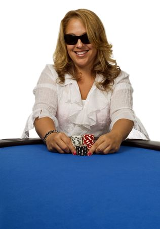 Attractive woman pushes her poker chips forward on a blue felt poker table.
