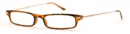 gafas de lectura: Un par de gafas, de lectura con los brazos extendidos, sobre un fondo blanco.  Foto de archivo