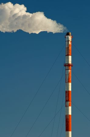 Smoke billows from a smokestack against a blue sky. photo