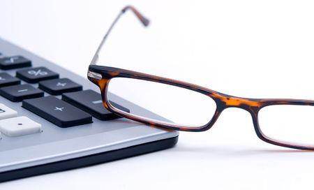 gafas de lectura: Leyendo gafas sentado en el borde de la calculadora sobre un fondo blanco.  Foto de archivo