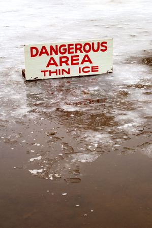 A pond covered in a thin layer of ice with some open water, and a sign signifying the danger.