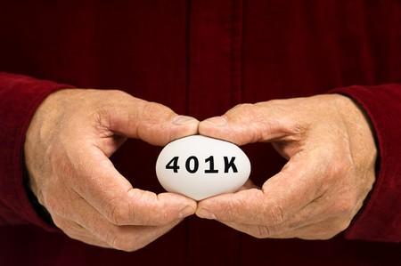 letras negras: Blanco de huevo con 401k escrito en �l con letras negras. Celebrado por un hombre en una camisa roja.