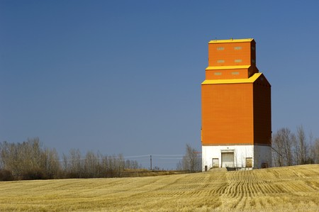 One solitary orange grain elevator stands at attention with grain stubble surrounding it. photo