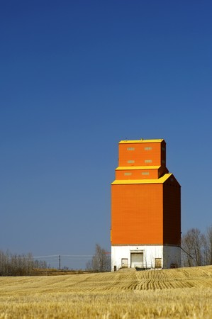 One solitary orange grain elevator stands at attention with grain stubble surrounding it. Stock Photo - 6962944