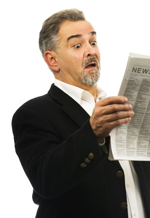 One mature man looks surprised; shocked; awestruck while reading a newspaper. Stock Photo