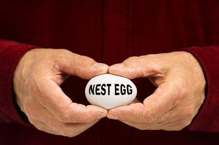 Man holds a white egg with NEST EGG written on it, symbolizing the fragility of money matters and the proverbial 'nest egg.' Standard-Bild