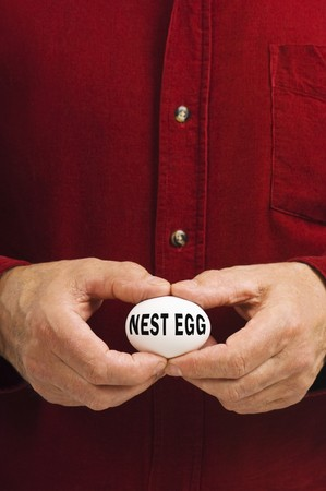 money matters: Man holds a white egg with NEST EGG written on it, symbolizing the fragility of money matters and the proverbial nest egg.