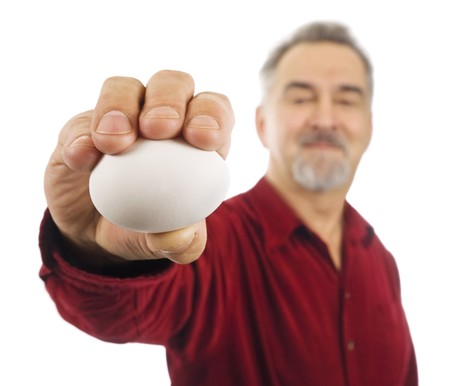 Mature man holds a white egg in his outstretched hand.