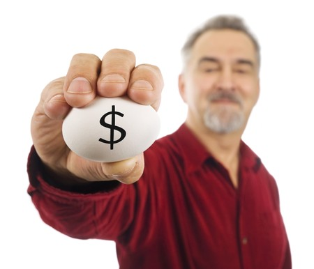 money matters: Mature man holds an egg with a dollar sign ($) on it. Symbolizes how fragile the economy is; how careful one has to be with money matters. Stock Photo