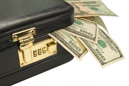 A locked briefcase with american currency coming out of the corner. photo