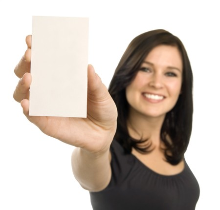A brunette woman holds a blank business card at arm's length. Focus is on the card, with face out of focus.