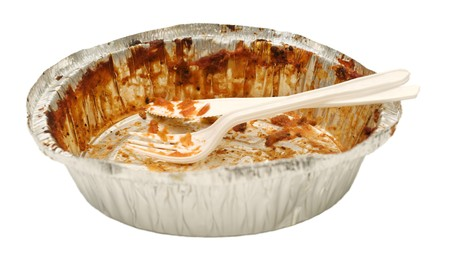 emptied: Plastic white knife and fork sitting in an aluminum tray take out tray emptied of its food contents.