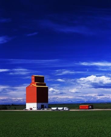 A grain truck pulls away from a grain elevator on the prairies. photo