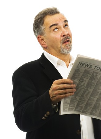 Mature man, while holding his newspaper, looks skyward with a look of despair.