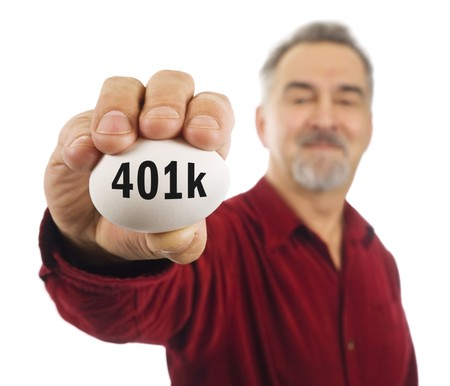 Mature man holds a white nest egg with 401k on it. 401k is a popular American investment tool.