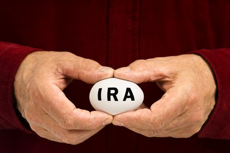 A man holds a white nest egg with IRA written on it, symbolizing the fragility of money matters and the proverbial nest egg. An IRA is an Individual Retirement Arrangement, a retirement plan popular in the United States.
