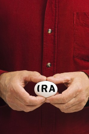 A man holds a white nest egg with IRA written on it, symbolizing the fragility of money matters and the proverbial nest egg. An IRA is an Individual Retirement Arrangement, a retirement plan popular in the United States. photo