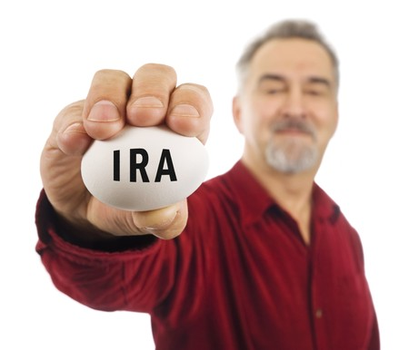 Mature man holds a white nest egg with IRA on it. IRA is an Individual Retirement Account, a popular investment tool in the United States of America.