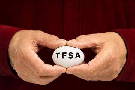 A man holds a white nest egg with TFSA written on it, symbolizing the fragility of money matters and the proverbial 'nest egg.' TFSA is a Tax Free Savings Account, popular in Canada.