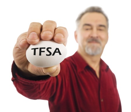 Mature man holds a white nest egg with TFSA on it. TFSA is a tax free savings account, a popular investment tool used in Canada.