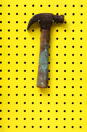 Old hammer with paint marks hangs from metal hook. Wooden handle with metal head. photo
