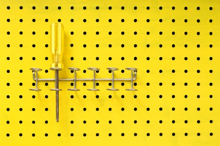 One yellow Phillips screwdriver sits in a rack on a yellow pegboard. Stock Photo
