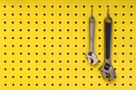 Pair of metal wrenches hang together off of hooks on yellow pegboard. photo