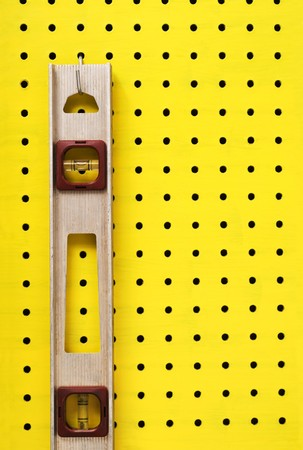 Old level hangs from a hook on yellow pegboard. photo