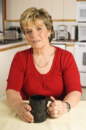 Woman sitting in her kitchen with a mug in her hand, taking a break Stock Photo