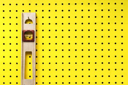 Old level hangs from a hook on yellow pegboard. Stock Photo - 7077213